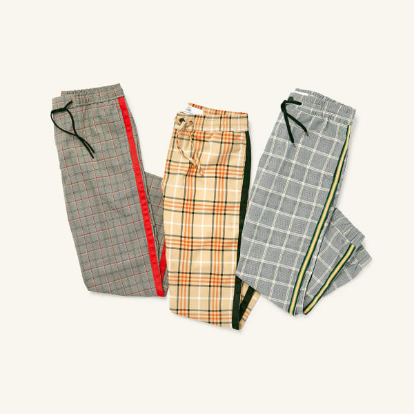 Three pairs of plaid men's pants laid flat on a white background.