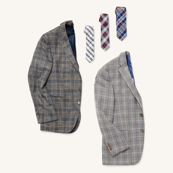 Two plaid men's sports coats and three plaid ties laid flat on a white background.