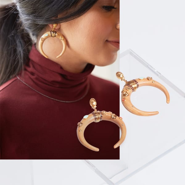 Statement earrings with a solid-colored turtleneck