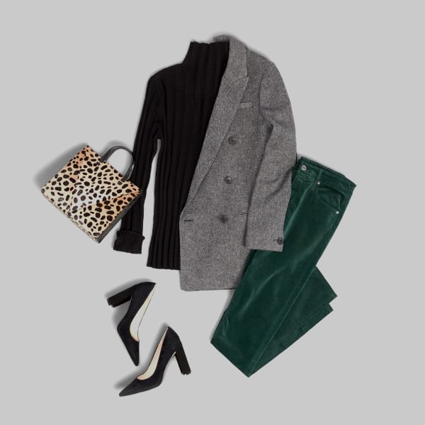 Women's outfit with green velour pants, black wedges, cheetah print purse, black turtleneck and a grey blazer laid flat on a grey background.