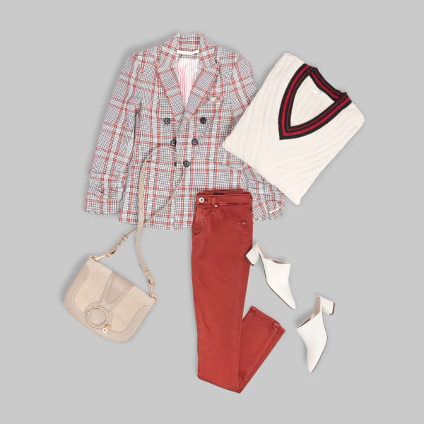 Women's outfit with red corduroy pants, white v-neck sweater, white shoes, tan purse and a plaid blazer laid flat on a grey background.