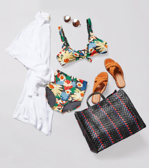 floral swimsuit with a white cover-up and beach tote bag