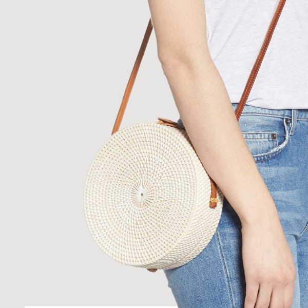 A round woven basket bag in cream with a brown strap