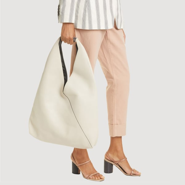Woman carrying a hobo bag in white