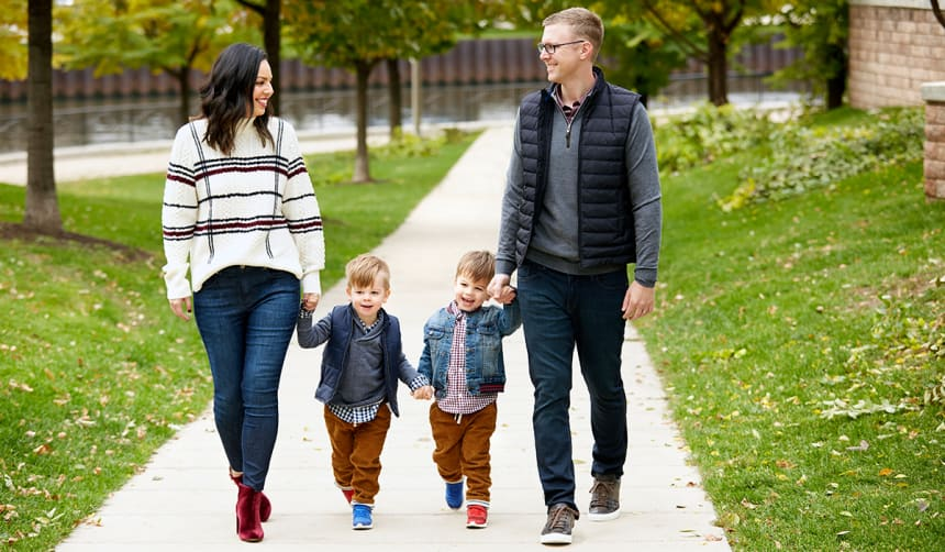 A family of four (mom, dad and two young boys) walking in a park in autumn.