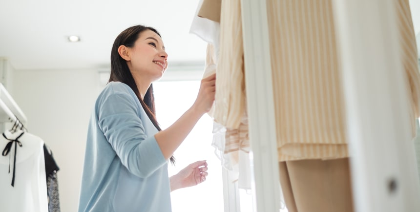 women in a blue shirt smiling while in her closet