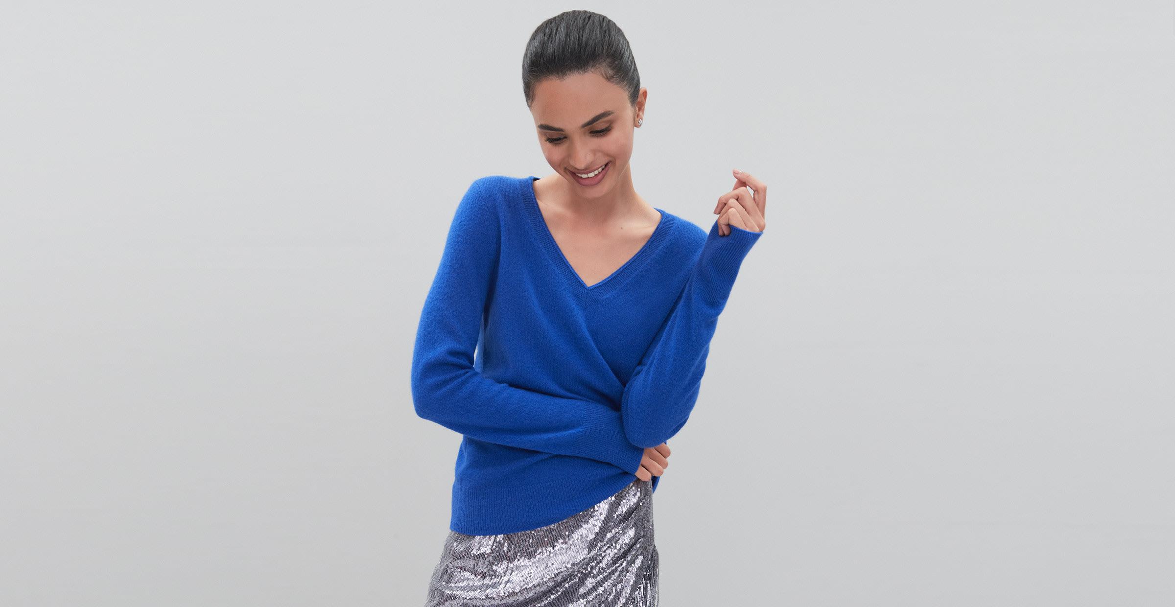 Woman wearing blue sweater and silver metallic skirt.