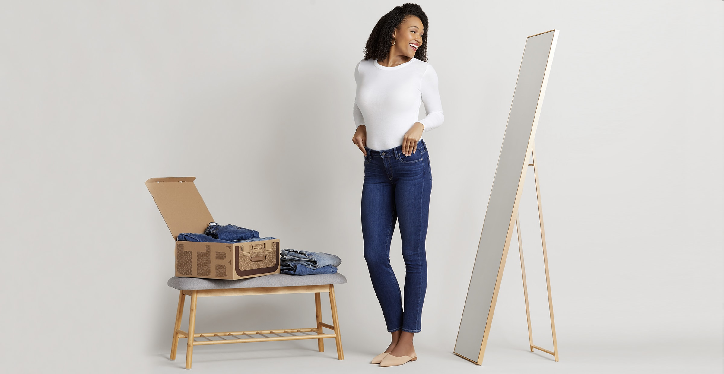 A women trying on a pair of dark denim jeans