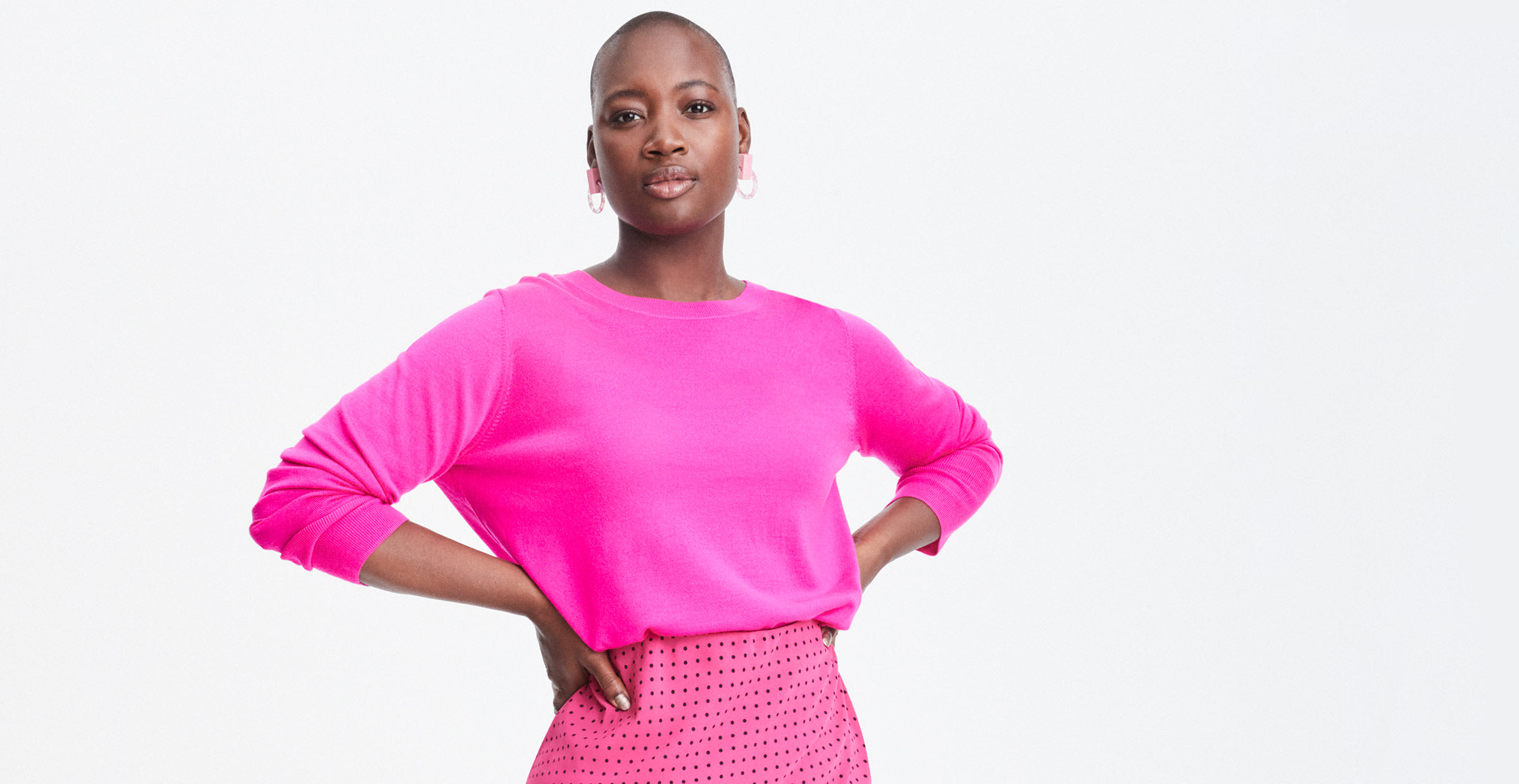 Women in a bright pink sweater and skirt