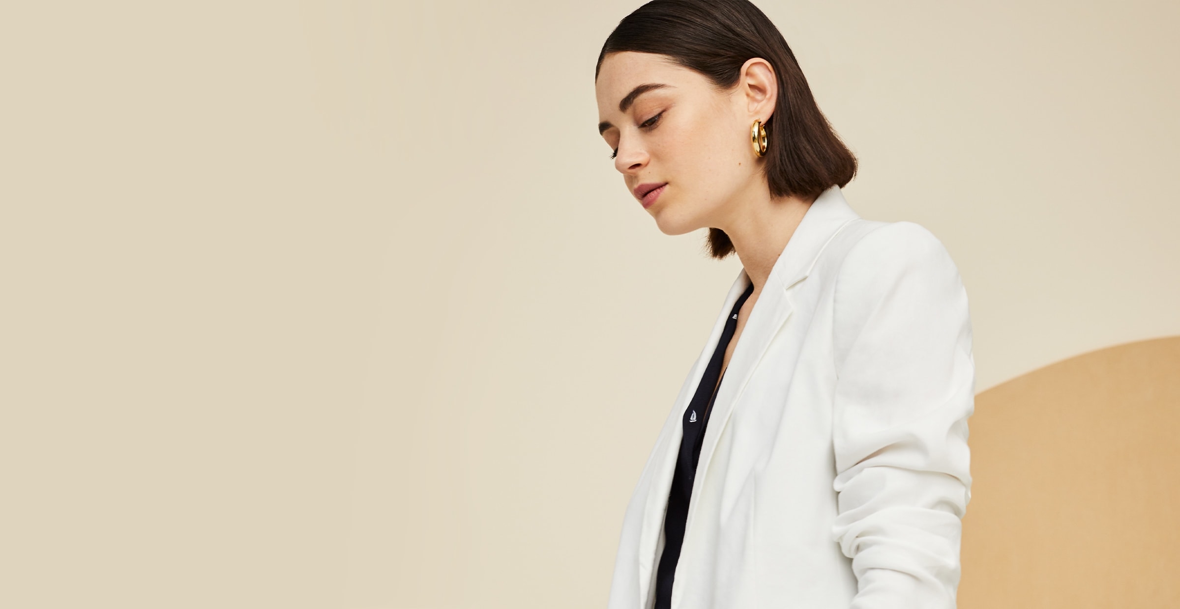Women in a white blazer with gold hoops