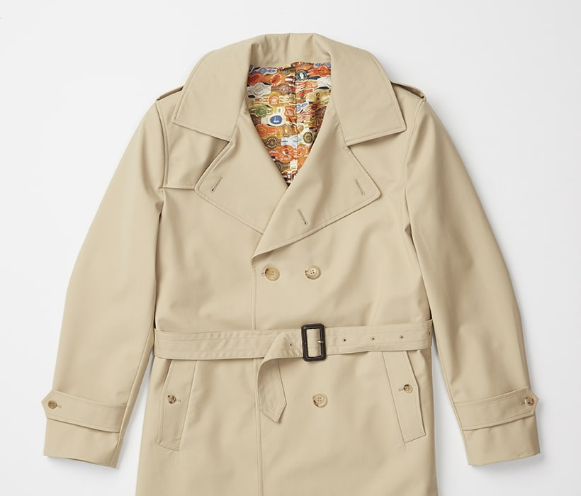 Double-breasted raincoat with storm flaps, epaulettes, and removable belt