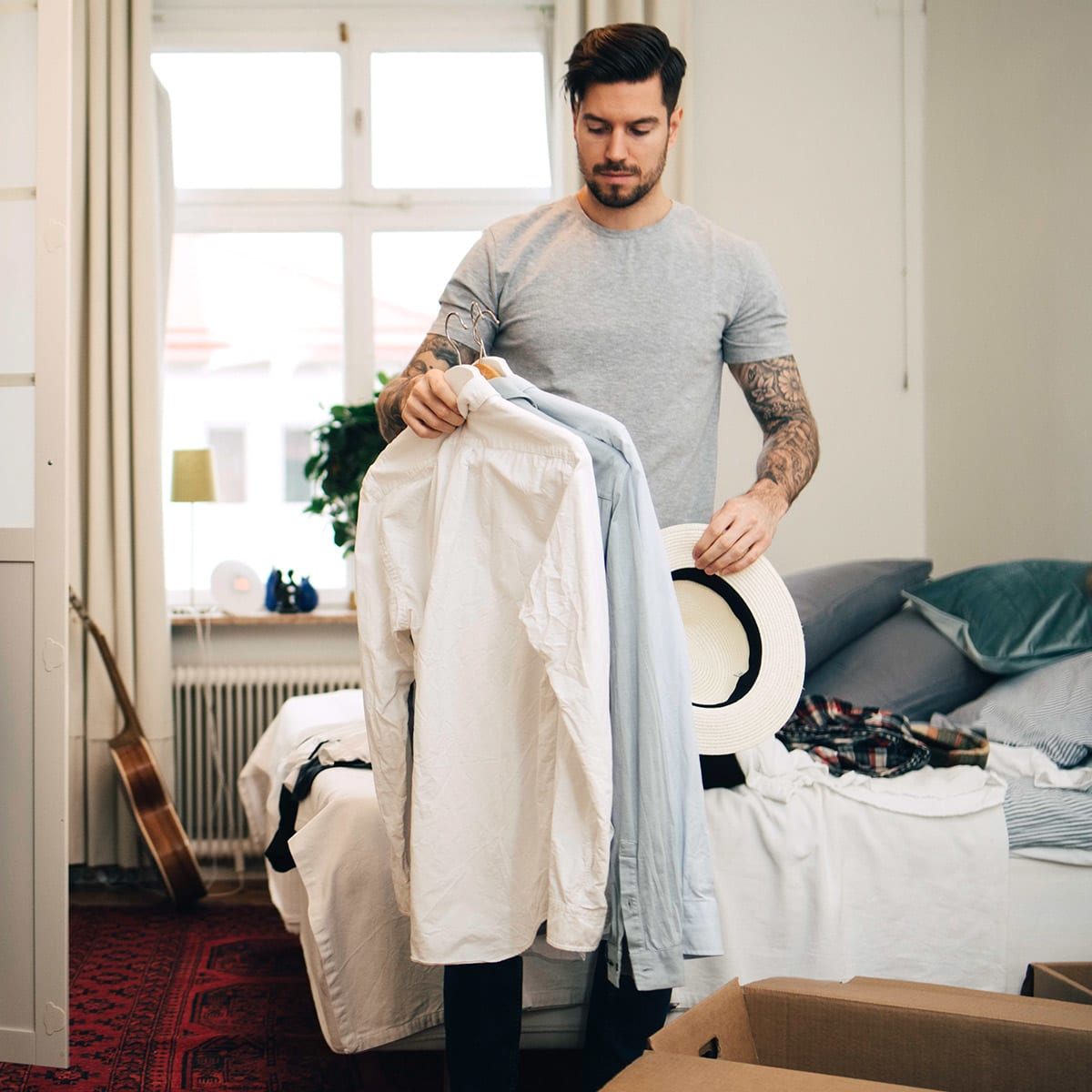 Man holding several shirts (on hangers) in his bedroom.