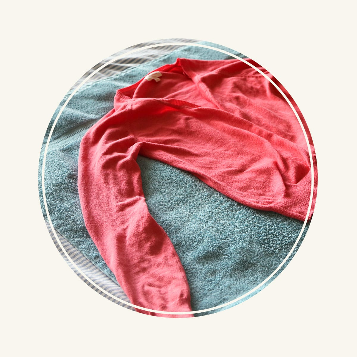 Women's pink cashmere sweater laying on a turquoise towel after washing.