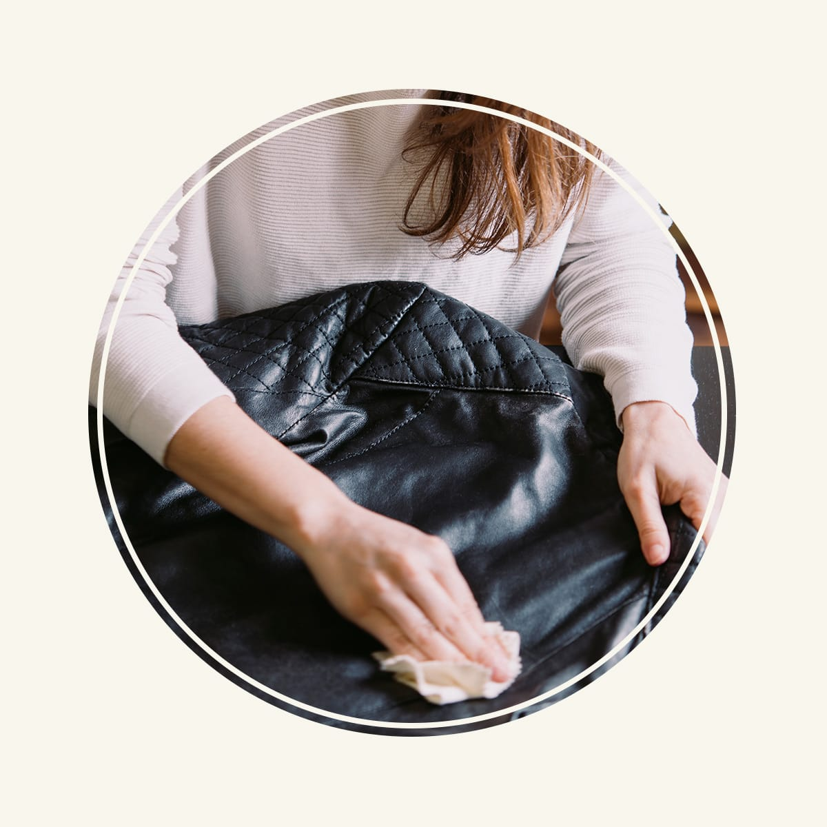 Woman cleaning black leather jacket.
