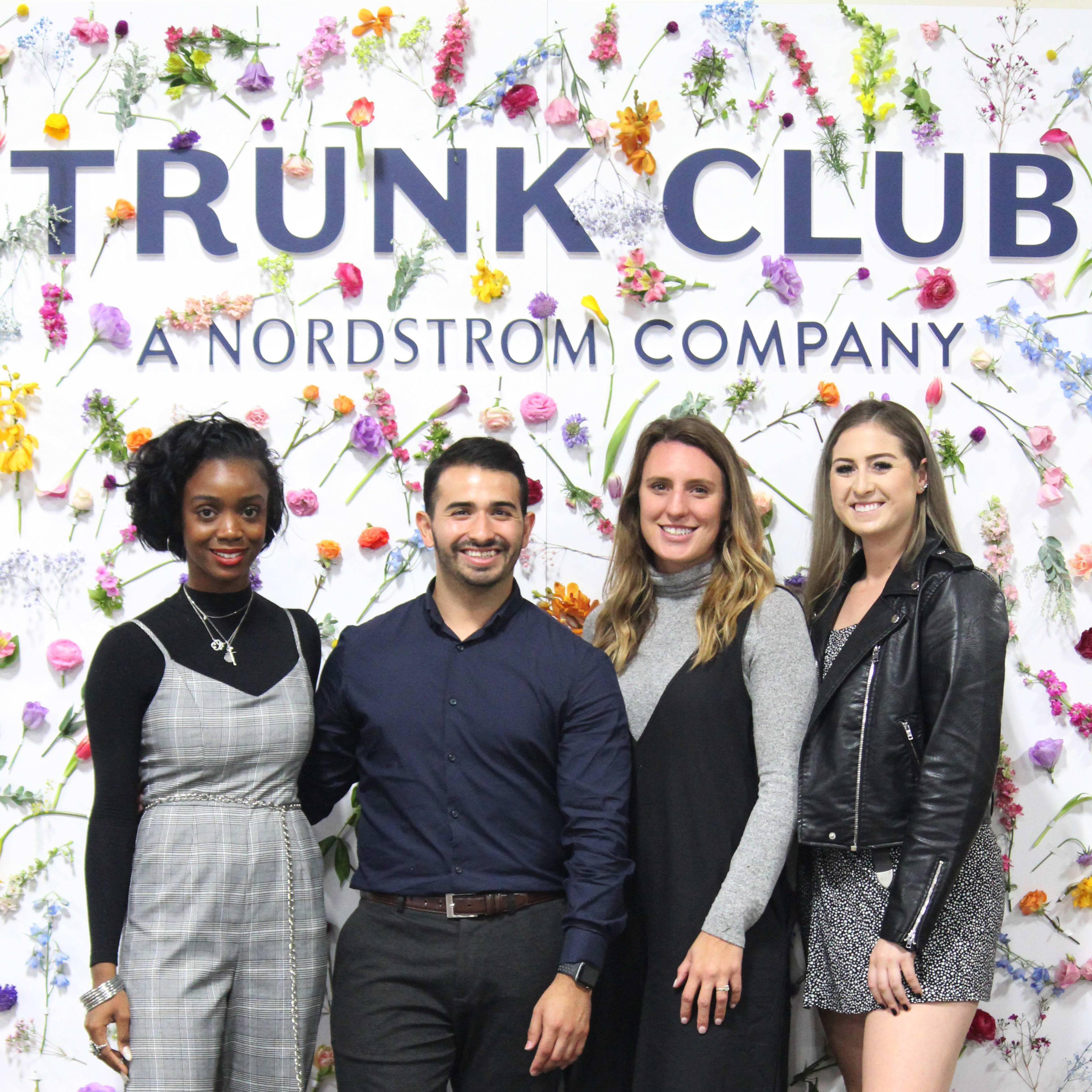 Group of four in front of a Nordstrom Trunk Club Instagram wall covered in flowers.