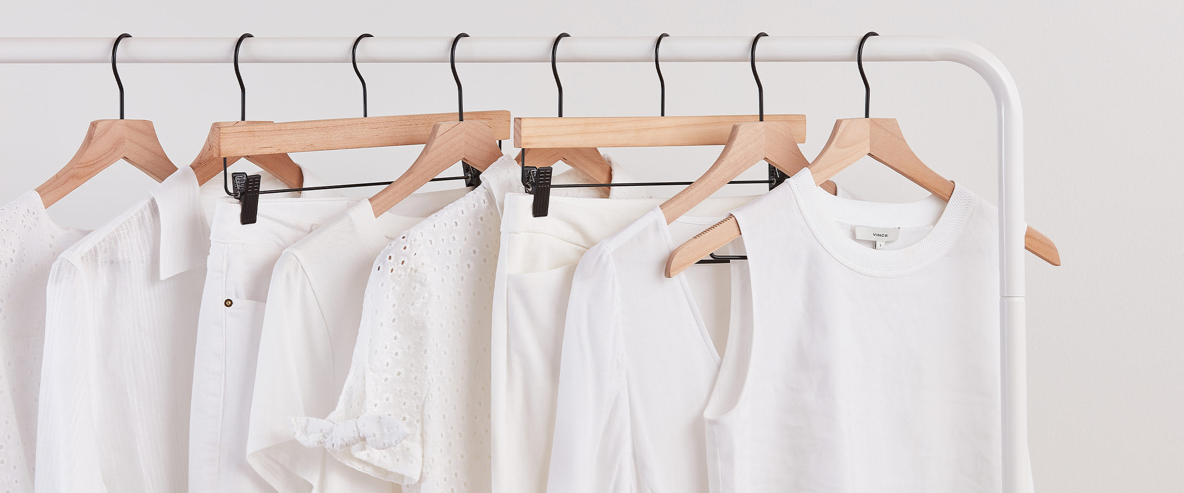 Hanging white clothes on clothing rack