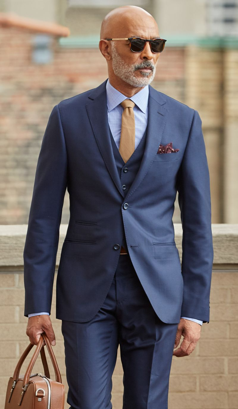 Business look - navy blue suit with overcoat in hand.