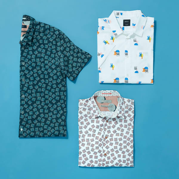 Three collared shirts featuring geometric patterns folded neatly and laid flat on a blue background.