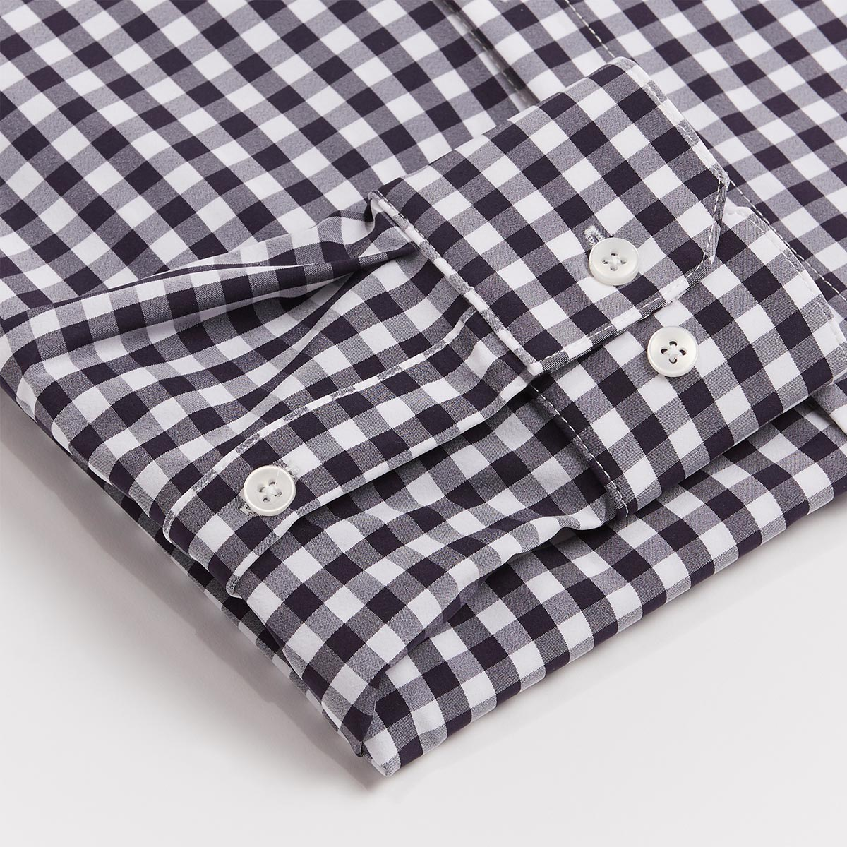 Black and white checkered collared work shirt neatly folded with sleeve in foreground to show fabric details.