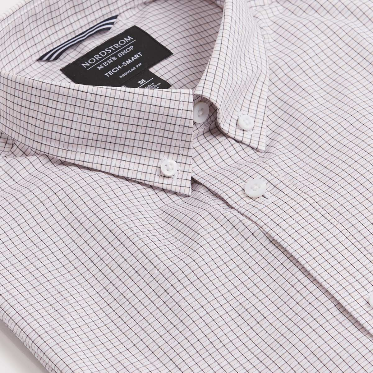 Pink and white striped shirt folded neatly to show off crisp collar, Nordstrom tag and button details.