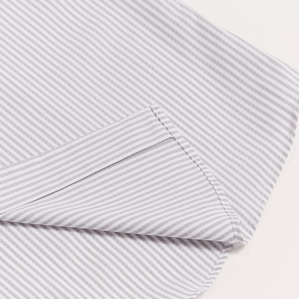 Grey and white striped shirt folded neatly with hem revealed to show off the quality of the fabric and stitching details.
