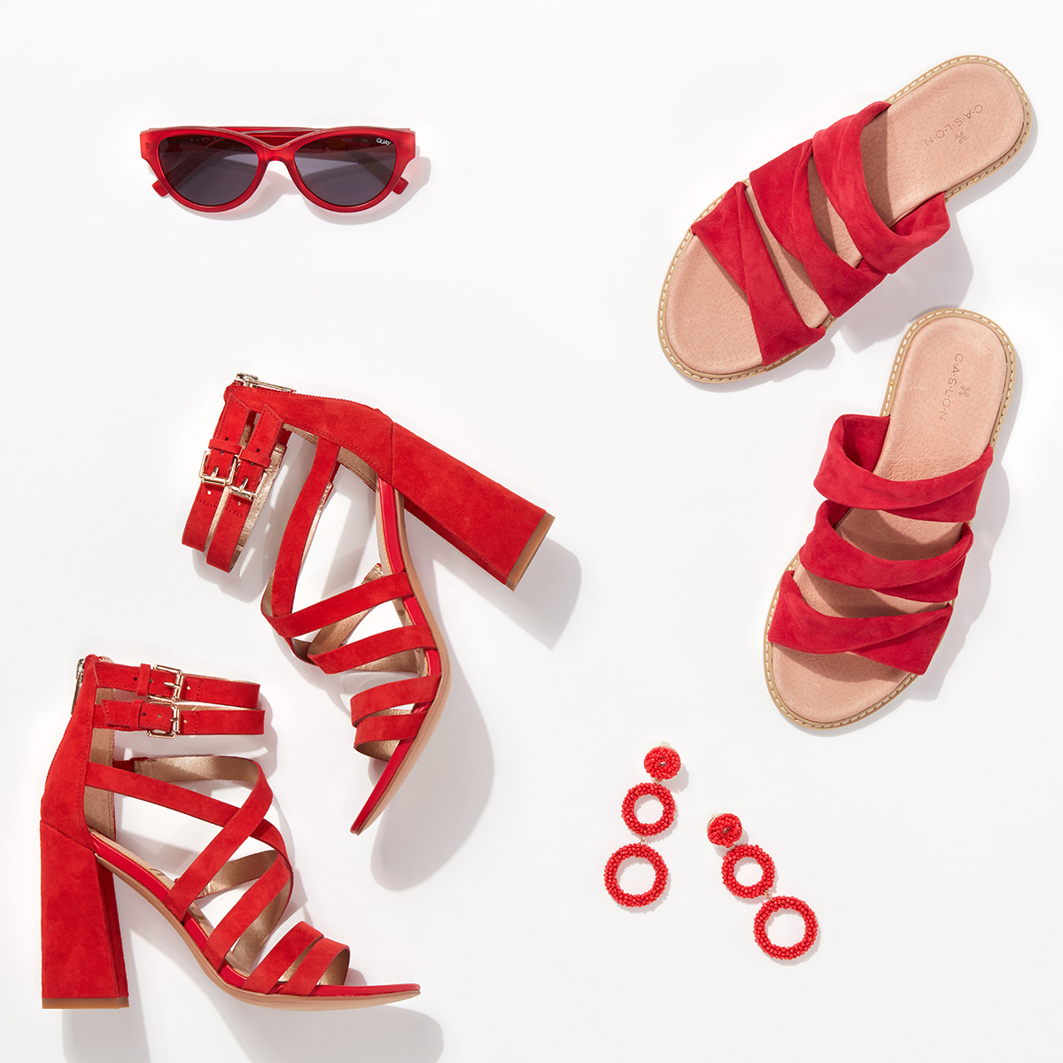A pair of strappy, red heels with gold buckles, a pair of red hoop earrings and a pair of red sunglasses arranged neatly on a white background.