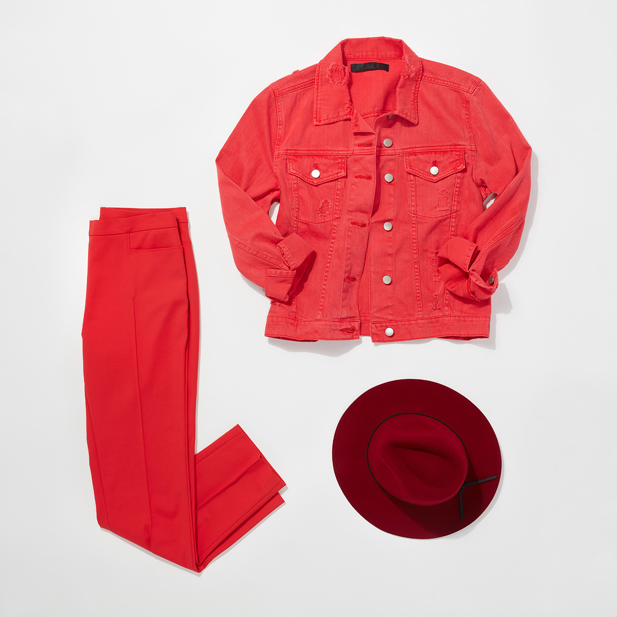 Three articles of red clothing - a red jean jacket, red slacks, and a dark red fabric hat arranged neatly on a white background.