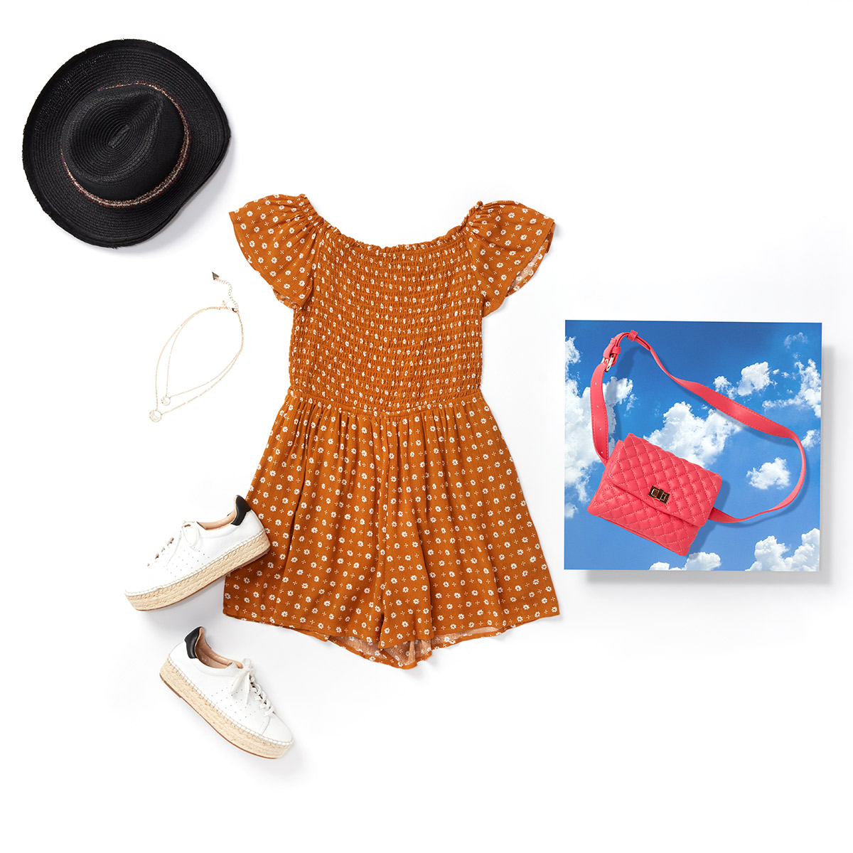 Brown romper, black hat, tassel necklace and white espadrilles sneakers laid flat on a white background.