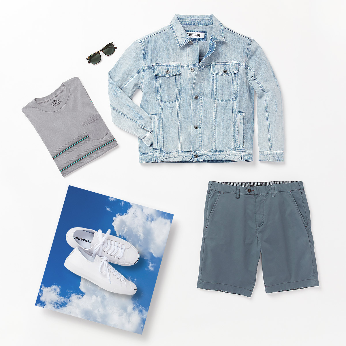 Grey t-shirt, light wash denim jacket, blue shorts, sunglasses and white Converse sneakers laid flat on a white background.