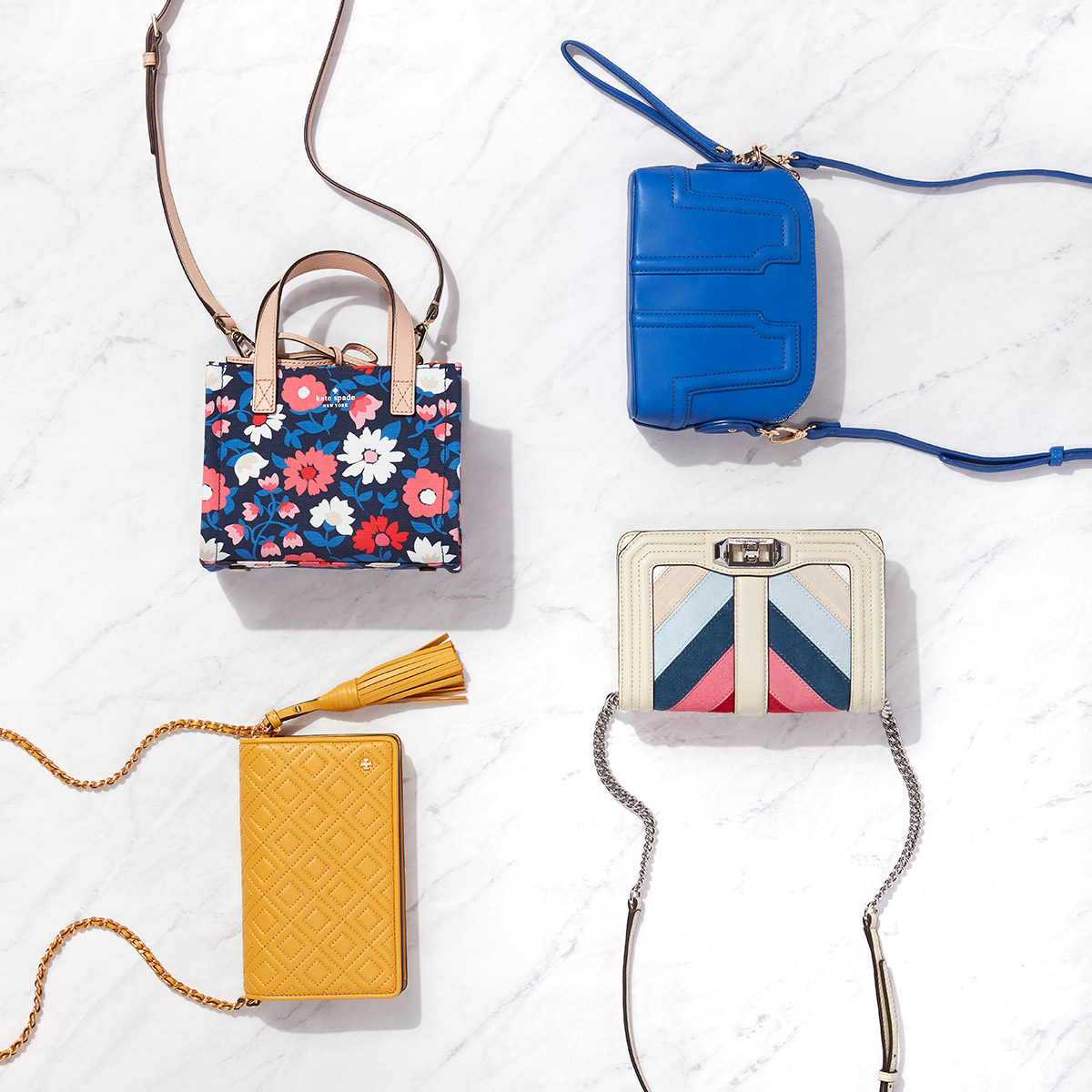 Four mini hand bags in a variety of patterns and colors laid flat on a marble background.