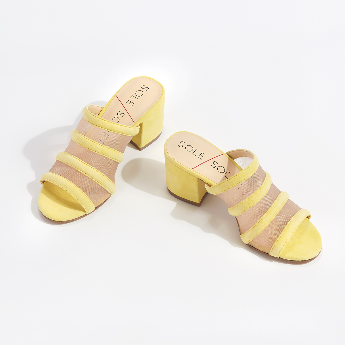 A pair of bright yellow heels with sheer panels sitting on a white background.