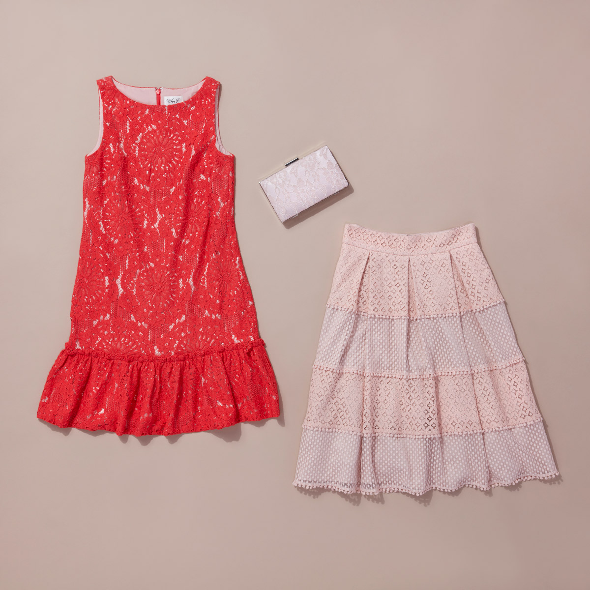 Red lace sleeveless dress, pink lace skirt and a light pink clutch adorned with lace laid flat on a taupe colored background.