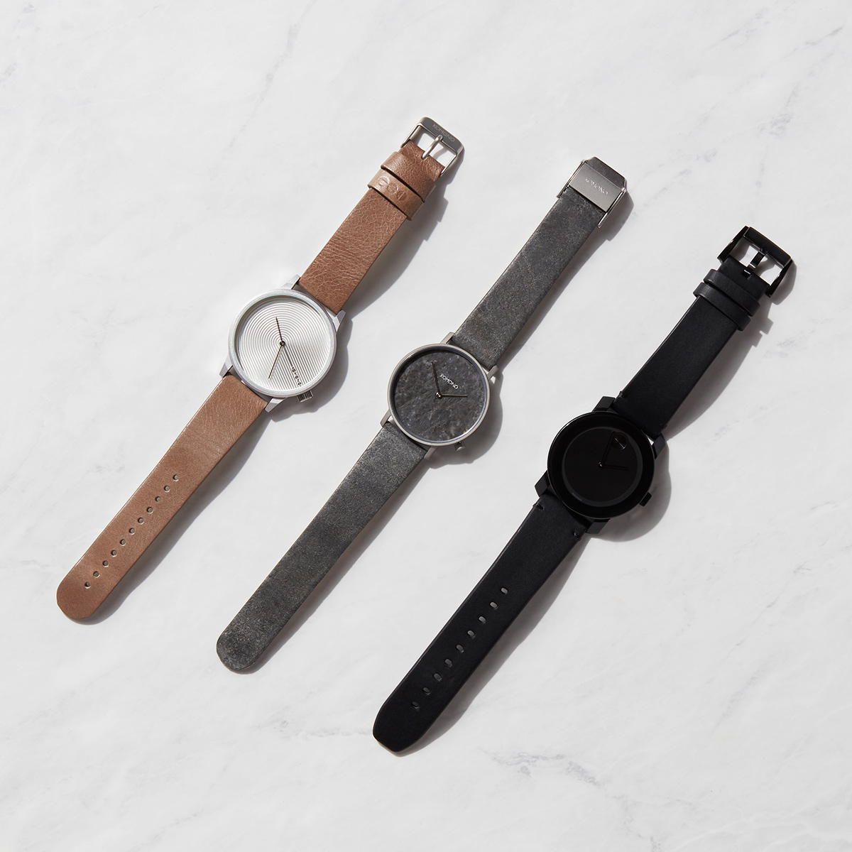 Three neutral colored watches organized in a diagonal composition laid flat on a marble background.