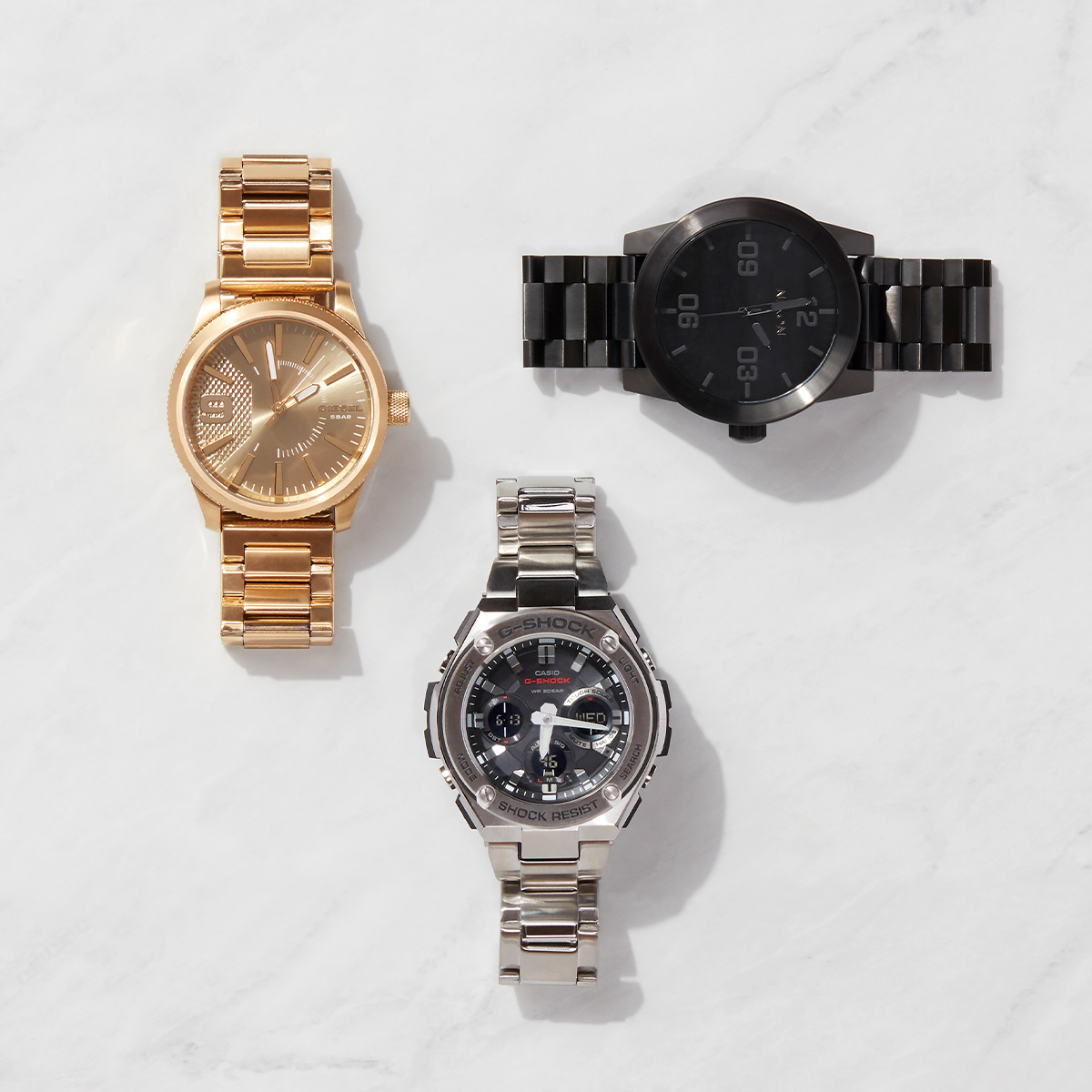 Three metallic bracelet watches laid flat on a marble background.