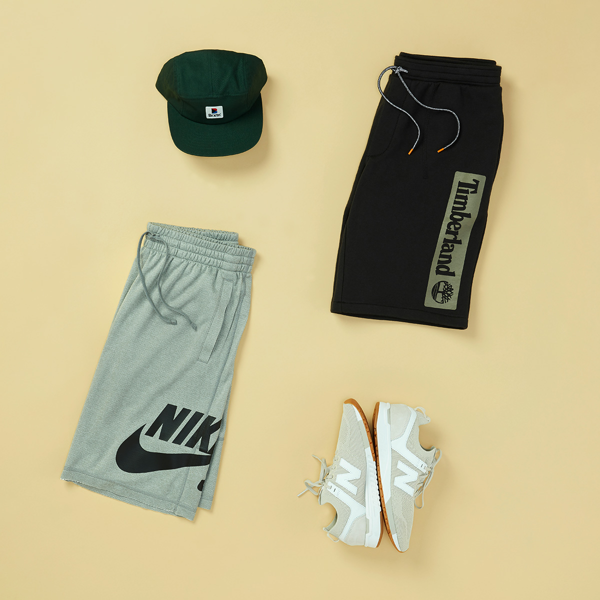 Four articles of men's clothing featuring logos - a hat, Timberland shorts, Nike shorts, and Nike sneakers - laid flat on a light yellow background.