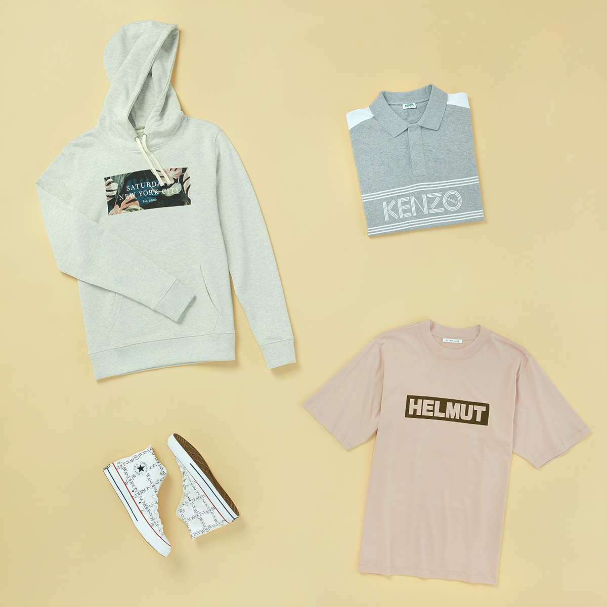 Four articles of men's clothing featuring logos - Converse sneakers, a Helmut Lang tee, a Kenzo polo, and a Saturdays NYC hoodie - laid flat on a light yellow background.