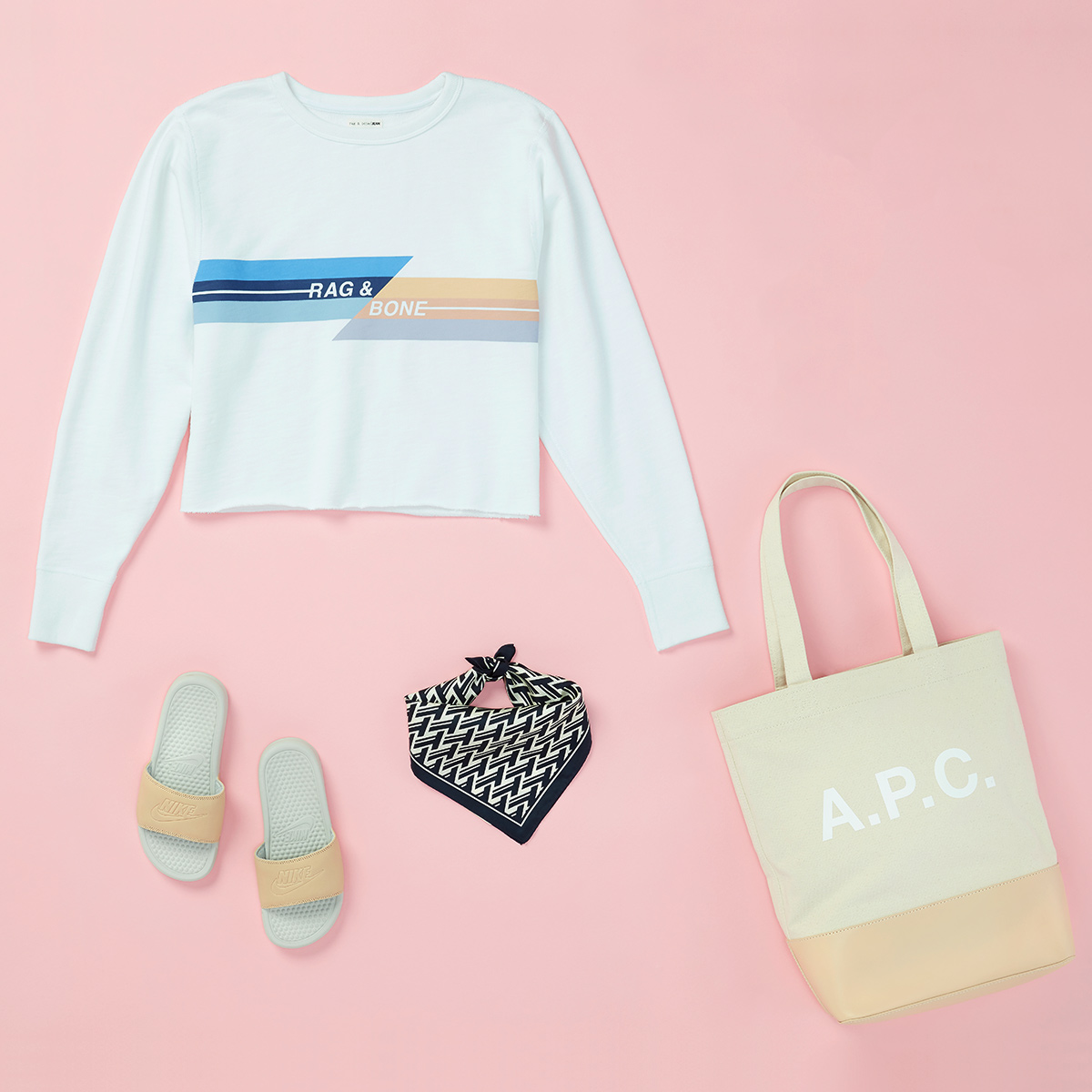 Four women's fashion items - a tote bag, athletic slip-on sandals, a black & white scarf, and a white sweatshirt laid flat (with garment logos prominently displayed) - on a pink background.