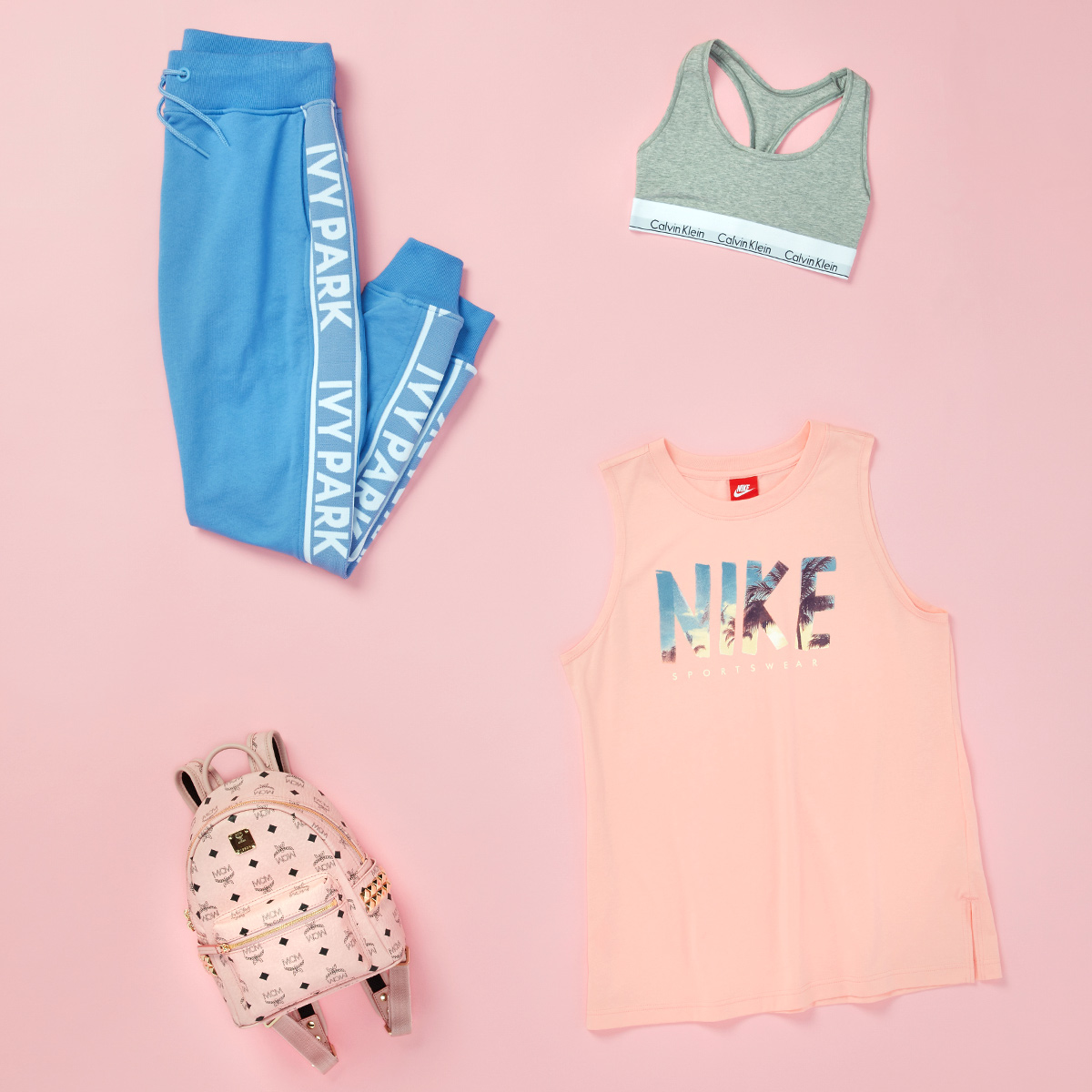 Four women's fashion items - jogging pants, a patterned backpack, a sports bra, and a t-shirt laid flat (with garment logos prominently displayed) - on a pink background.