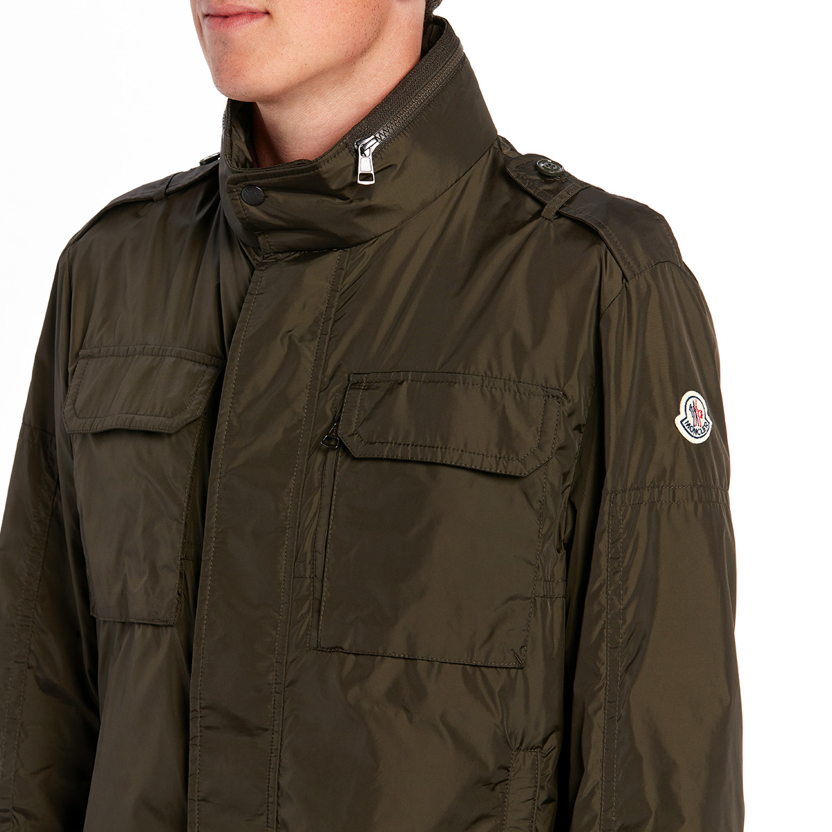 Close-up shot of a man wearing a zipped up hunter green parka.