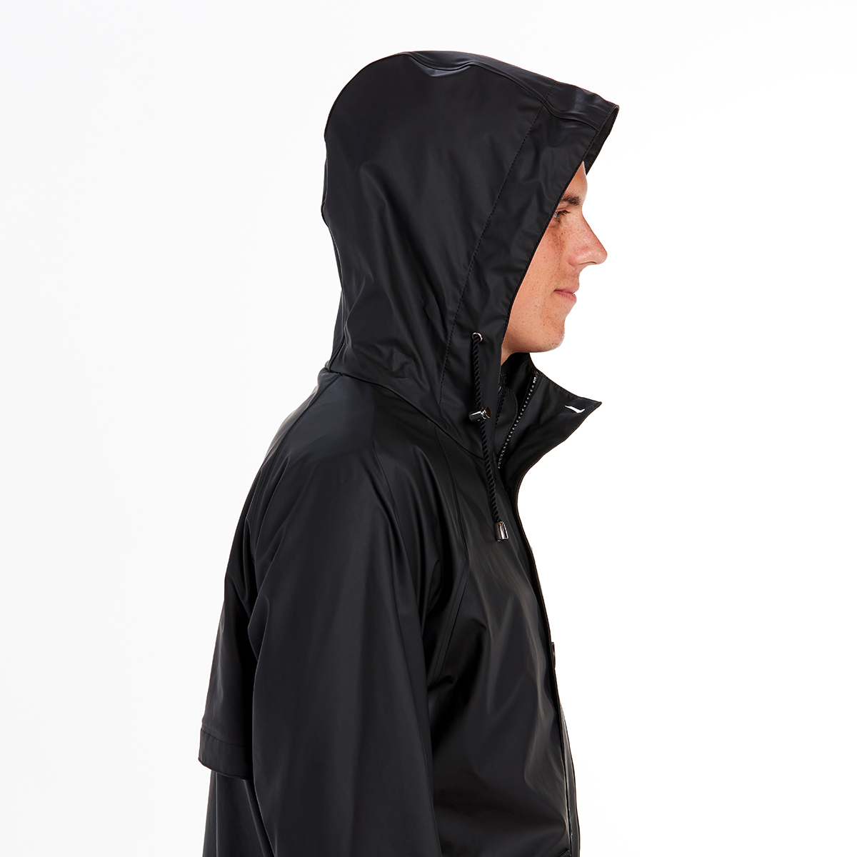 Man in profile wearing a navy blue parka with the hood extended, protecting his head from the weather.