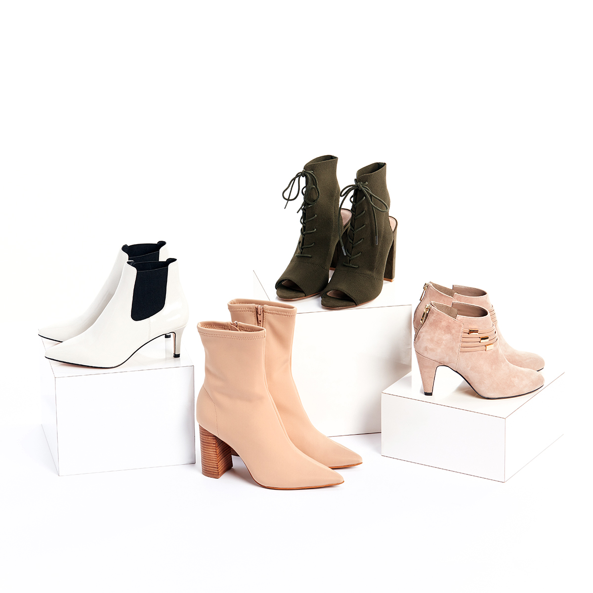 Four pairs of women's booties in white, olive and beige tones stacked on white boxes on a white background.