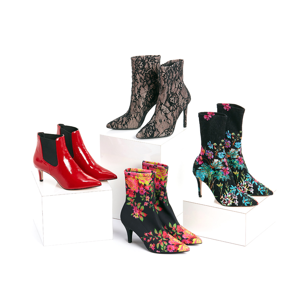 Four pairs of women's booties in bright red, lace and floral patterns stacked on white boxes on a white background.