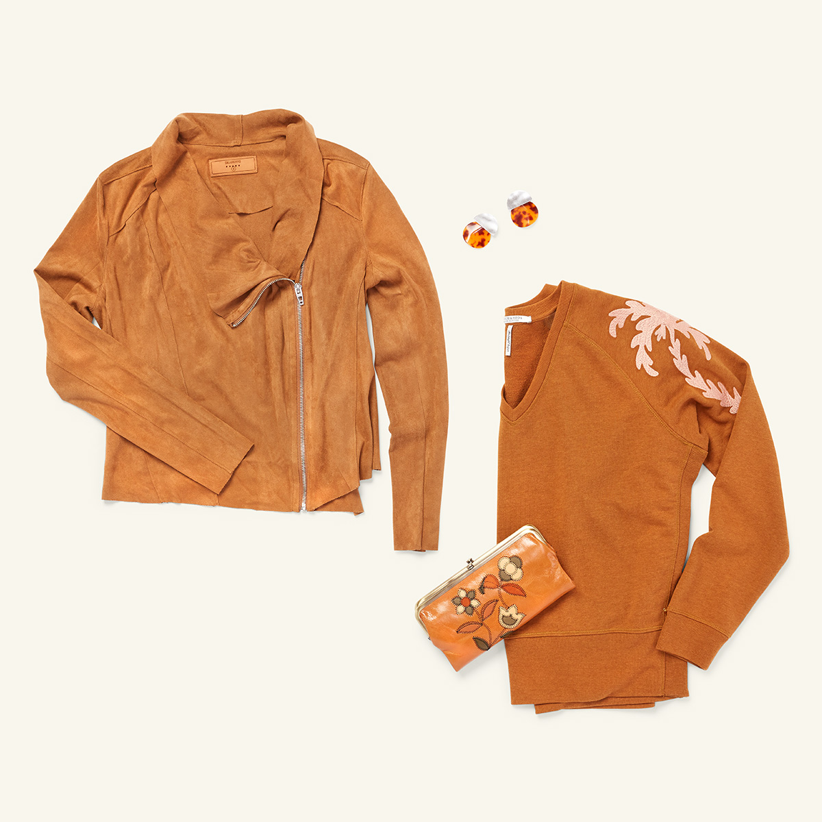 Four items of women's clothing - a faux suede jacket, a pair of tortoise shell earrings, a v-neck sweater and a brown leather clutch - laid flat on a white background.