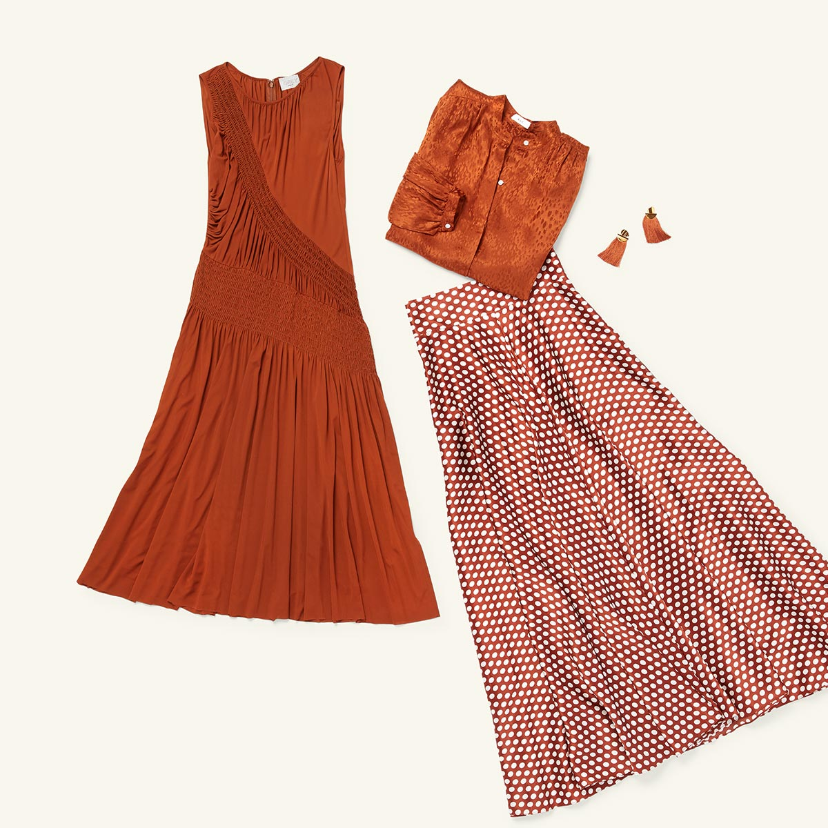 Four items of women's fashion - a pair of fringed earrings, a silk blouse, a flowing dress and a pleated skirt - laid flat on a white background.
