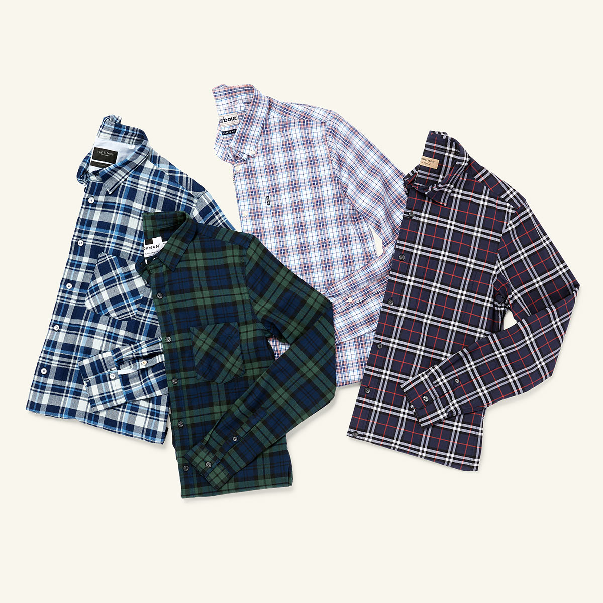 Four plaid men's shirts laid flat on a white background.