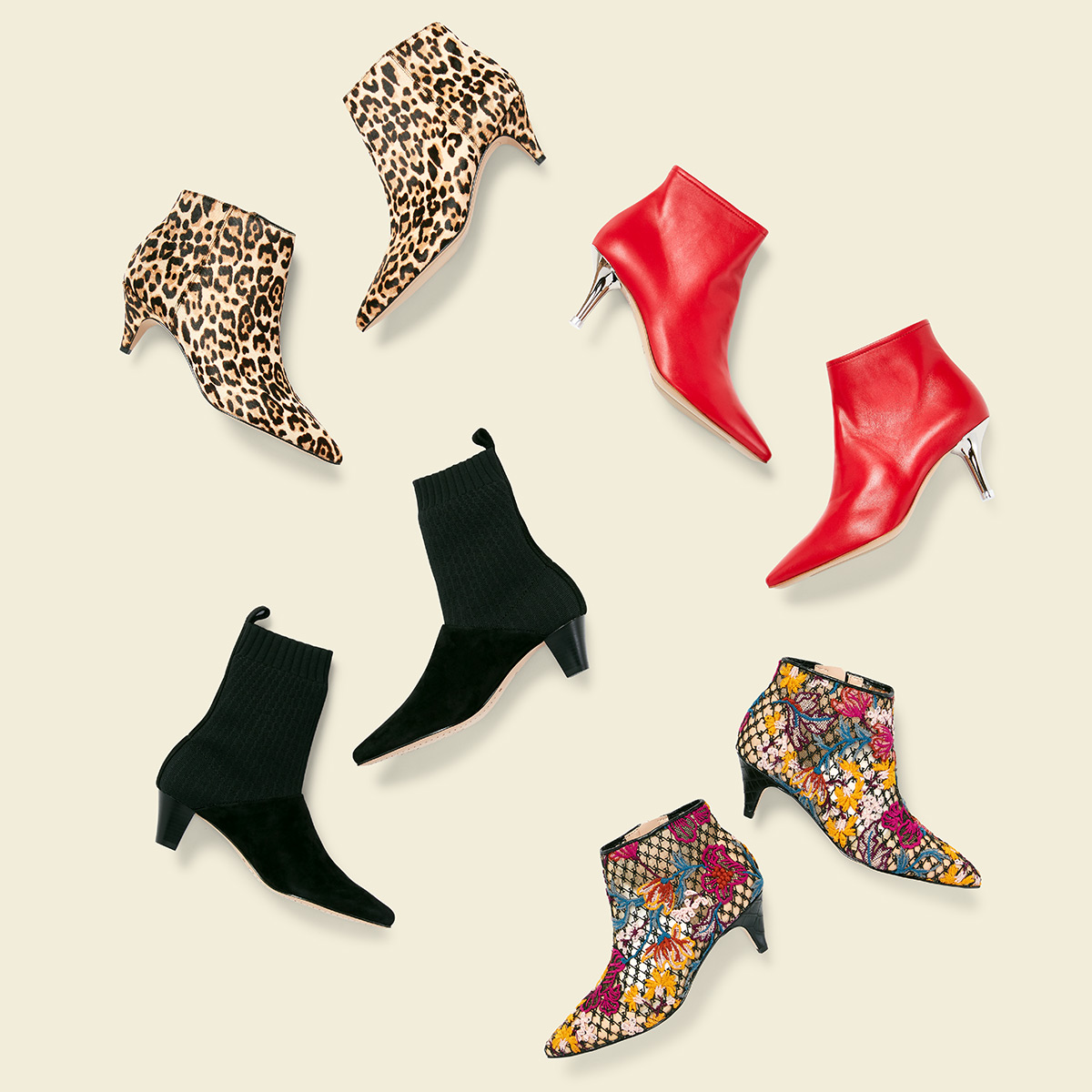 Four pairs of kitten heeled boots - one bright red, one in leopard print, one black with fabric tops, and one in floral print - laid flat on a cream background.