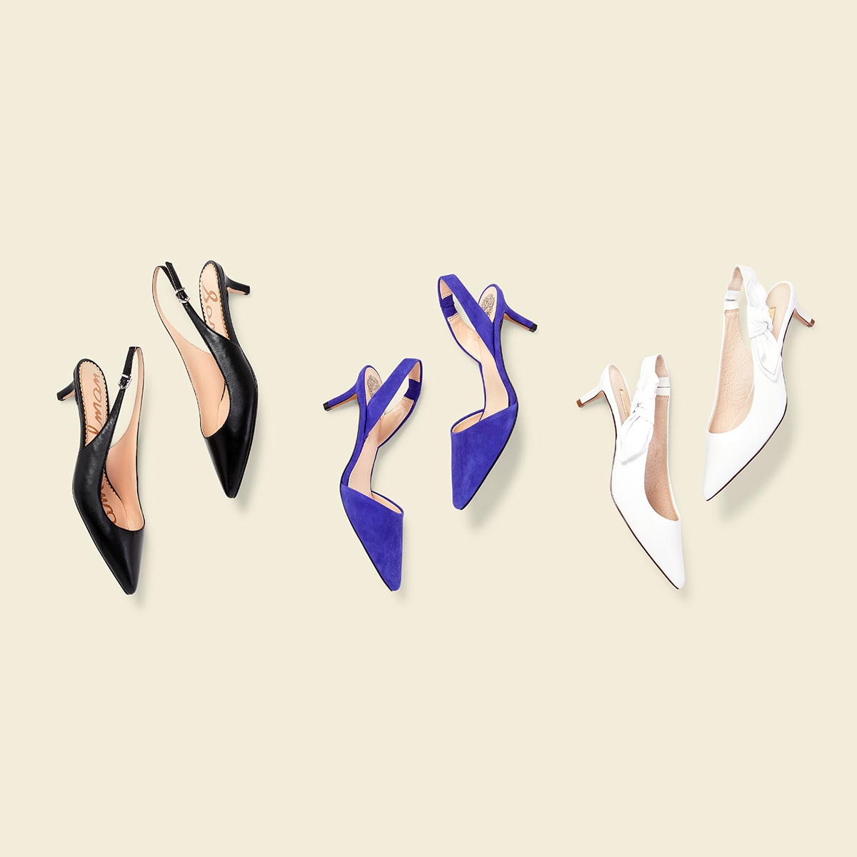 Three pairs of kitten heels - one white, one black and one in royal blue suede - laid flat on a cream background.