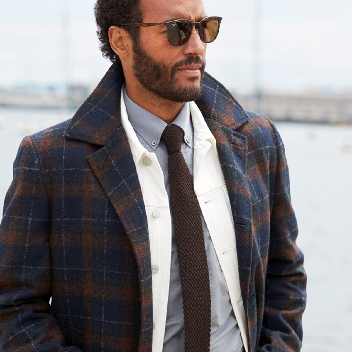 Male model standing outdoors wearing a jacket featuring oversized plaid.