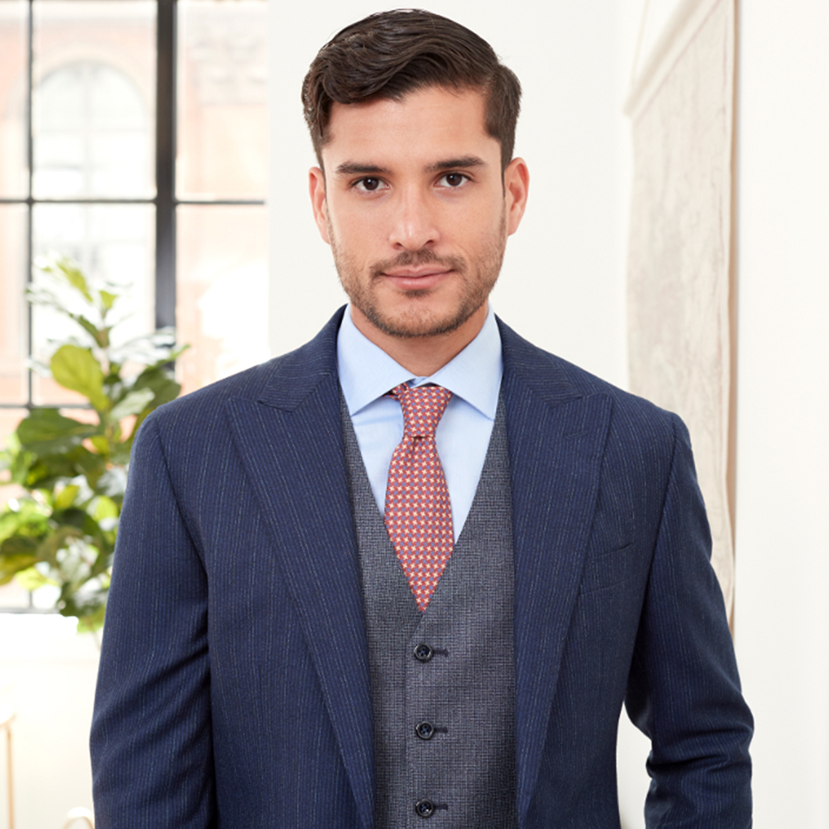Male model standing indoors looking directly at the camera wearing a pinstriped jacket.