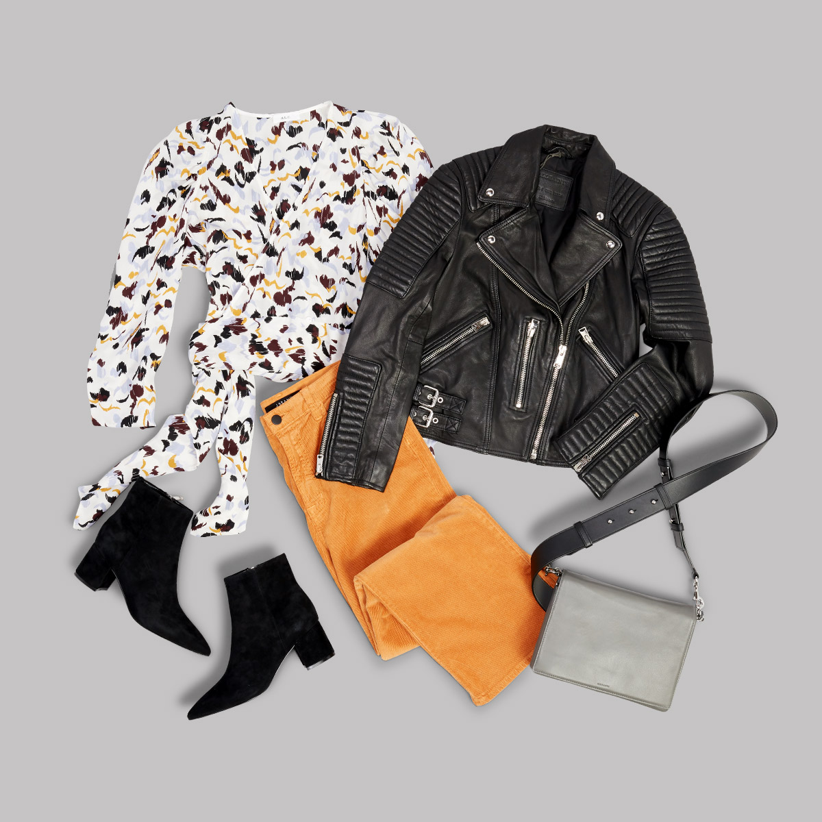 Women's outfit with gold pants, white shirt with floral print, black boots, grey purse and a black leather jacket laid flat on a grey background.